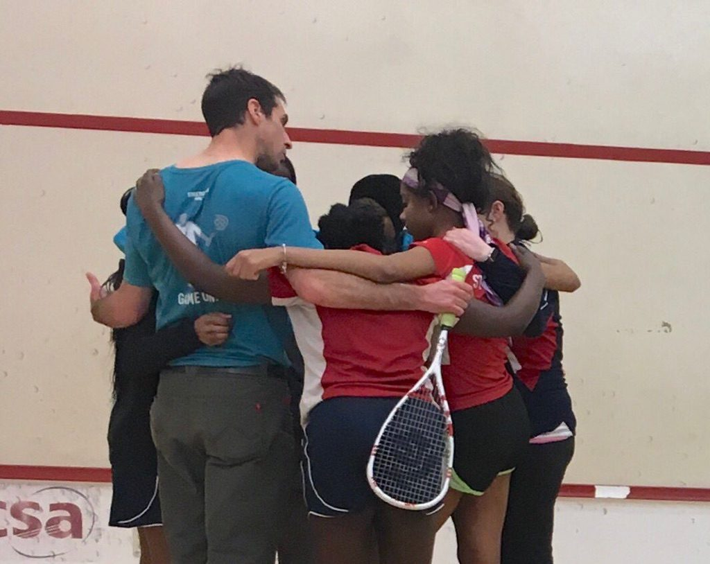 "Day 2: George offers his words of wisdom and encouragement (""Keep it tight!""), while huddling up with the GU17 ladies, prior to the semi-finals against Chicago's MetroSquash."